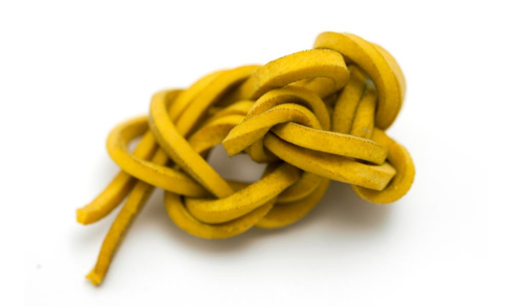 Elastique jaune emmêlé, posé sur un fond blanc